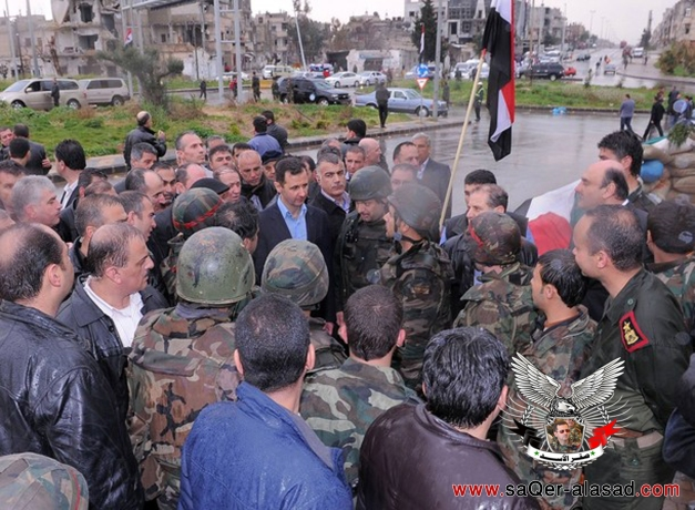 Syria's President Bashar al-Assad meets soldiers during a tour in the Baba Amr neighbourhood of Homs